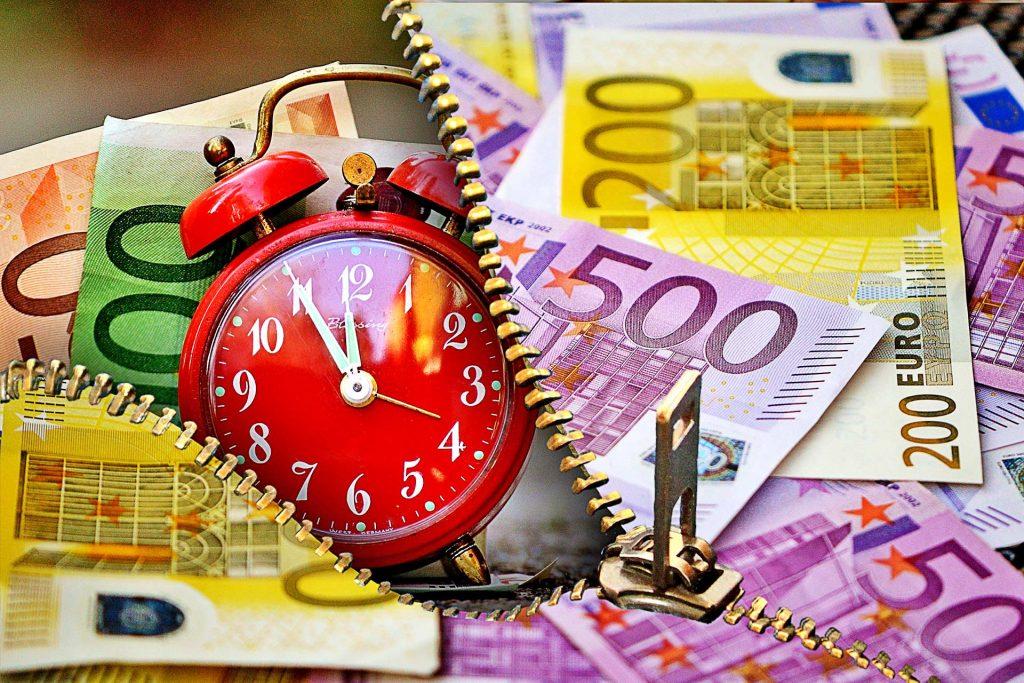 Geldscheine und Uhr die kurz vor zwölf anzeigt