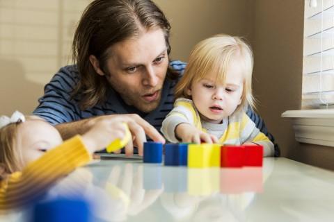 Vater spielt mit zwei Kindern mit bunten Klötzchen