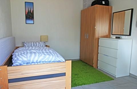Zimmer mit Bett, Schrank und Kommode
