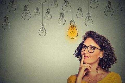 Junge Frau blickt nachdenklich hoch zu einer leuchteten Glühbirne
